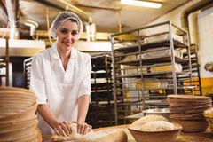 Boulanger féminin malaxant une pâte image stock