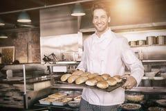 Boulanger heureux montrant le plateau avec du pain photos libres de droits