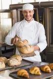 Boulanger heureux montrant le plateau du pain frais photographie stock libre de droits