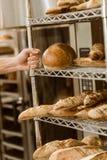 boulanger tenant des étagères avec les miches de pain fraîches photo stock