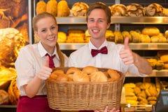 Boulangers dans la boulangerie avec le panier plein du pain photos stock