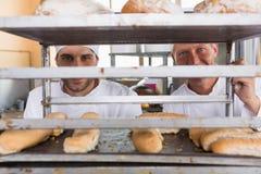 Boulangers de sourire regardant par le plateau du pain images stock