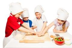 Boulangers heureux faisant des biscuits avec des coupeurs de biscuit Image libre de droits
