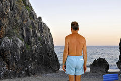 Boulder. Man with swimming-trunks approaching a boulder on the rocky shoreline Stock Photo