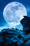 Boulder against blue sky with clouds and beautiful full moon at. Boulder with blue sky background and beautiful full moon behind cloud at night. Outdoor at Stock Image