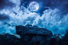 Boulder against blue sky with clouds and beautiful full moon at Stock Images