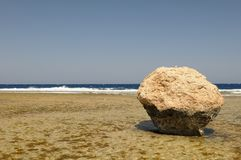 Boulder on beach by ocean Royalty Free Stock Images