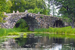 Boulder bridge over a pond Stock Image