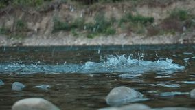 Boulder cae en el agua azul y hace el chapoteo grande y agita la cámara lenta metrajes