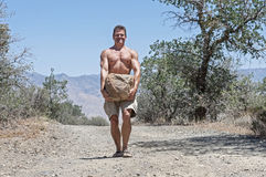 Boulder carry. Muscular shirtless Caucasian man struggles to carry heavy boulder on dirt road in rural outdoor scene Stock Photography