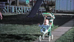 BOULDER, CO. USA - 1974: Little girl pushing baby brother around in a stoller. stock video