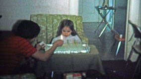 BOULDER, CO. USA - 1974: Mom lights birthday cake and fashionable girl sits at the table. stock footage