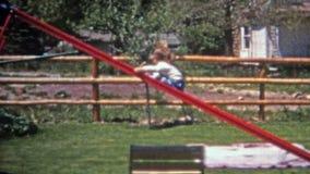 BOULDER, COLORADO 1952: Bambino che fa scorrere indietro giù lo scorrevole domestico residenziale ripido video d archivio