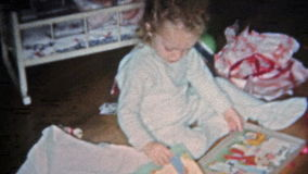 BOULDER, COLORADO 1951: Girl opening Christmas gift coloring book and other. stock video
