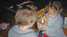BOULDER, COLORADO 1952: Girl opening Christmas gifts Bugs Bunny and Donald Duck books. stock video