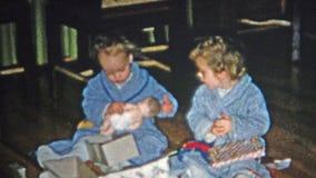 BOULDER, COLORADO 1952: Mamma che aiuta furtivo apertura del regalo di Natale con il bambino stock footage