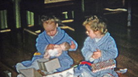 BOULDER, COLORADO 1952: Mom stealthily helping Christmas gift opening with child. stock footage