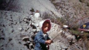 BOULDER, COLORADO 1952: Papà fresco che prende le figlie che pescano e che gettano le rocce stock footage
