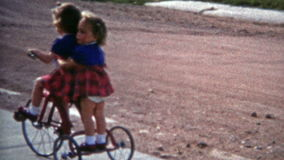 BOULDER, COLORADO 1952: Sisters riding tricycle suburban sidewalk street. stock video