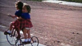 BOULDER, COLORADO 1952: Sorelle che guidano la via suburbana del marciapiede del triciclo archivi video