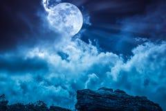 Boulder contra el cielo azul con las nubes y la Luna Llena hermosa en foto de archivo