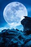 Boulder contra el cielo azul con las nubes y la Luna Llena hermosa en imagen de archivo