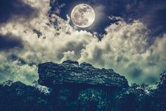 Boulder contra o céu com nuvens e a Lua cheia bonita outdoor Imagem de Stock