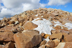 Boulder field near summit of mountain with patchy snow. stock images