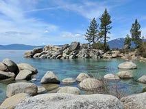Boulder gestreutes Wasser am Sand-Strand auf Lake Tahoe stockbilder