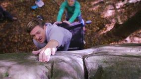 Boulder s'élevant dans les bois le grimpeur essayant de s'élever sur un rocher et les amis assurent le fond clips vidéos