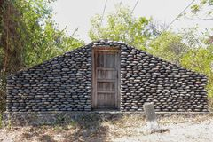 A boulder wall with closed wooden doors. Stone wall by the road in Bali Island, Indonesia. Enter the jungle. Mystical place with m. Ysterious building. Entrance stock photo