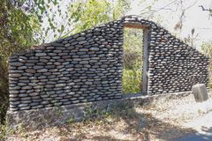 A boulder wall with open wooden doors. Stone wall by the road in Bali Island, Indonesia. Enter the jungle. Mystical place. royalty free stock photography