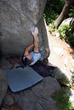 Bouldering / climbing / rock. A strong man bouldering on rock with a protective pad Royalty Free Stock Images