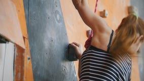 bouldering Een jonge vrouw die neer uit een rotsachtige muur binnen komen stock footage