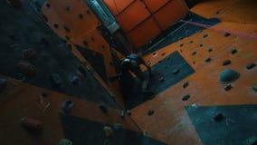 bouldering Een jonge vrouw die op een rotsachtige muur met een inspanning beklimmen stock video