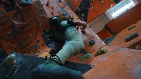 bouldering Een vrouw die op een rotsachtige muur binnen beklimmen stock videobeelden