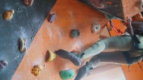 bouldering Een vrouw die op een rotsachtige muur met een inspanning beklimmen stock footage