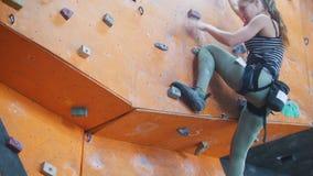 bouldering Eine junge Frau, die auf einer felsigen Wand klettert stock footage