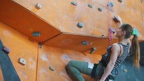 bouldering Eine junge Frau fängt an, auf einer felsigen Wand oben zu klettern stock video footage