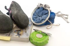 Bouldering Gear on White Background. Bouldering gear place on white background. Gear includes chalk bag, climbing shoes, medical tape, carabiner, and guide book Royalty Free Stock Photography
