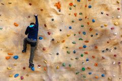 Bouldering - hombre que sube en la pared artificial de la roca fotos de archivo