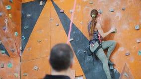 bouldering Un entraîneur observant s'élever de femme banque de vidéos
