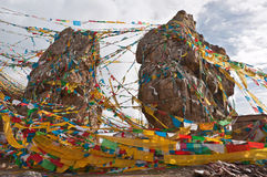 Boulders. The two boulders that a lot of color flags print with buddhist scriptures are intertwined Stock Photo