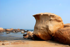 Boulders on the beach. A boulder shaped as wave by the seaside Royalty Free Stock Images