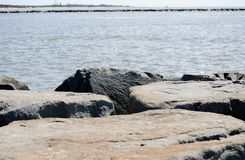 Boulders on a beach jetty Stock Image