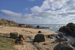 Rocky beach under with clouds stock photography