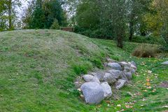 Boulders at the bottom. Boulders collected at the bottom of a hill with a bench in the distance Royalty Free Stock Images