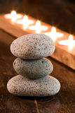 Boulders with candles. Grey Boulders with candles on a wooden background Stock Photos