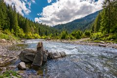Boulders on cascade of the forest river. Beautiful landscape in mountains on a bright day. lovely time spent while travel Carpathians Stock Image