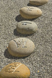 Boulders with Chinese characters. Boulders carved with Chinese characters lying in the gravel Stock Photography